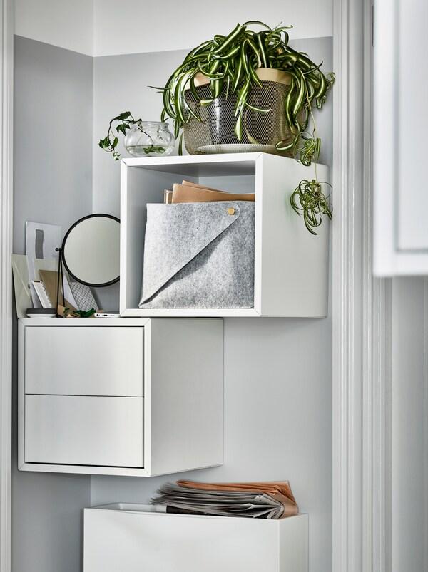 Uski zid pored vrata s belim EKET ormarićima, okačenim na zid, od kojih je jedan otvoren, a drugi s fiokama i biljkama na vrhu.