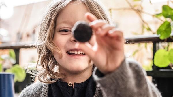 Usměvavé dítě s kulatým předmětem v ruce.