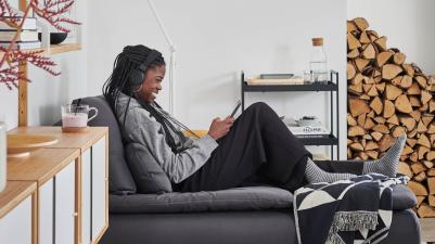 Uśmiechnięta kobieta, siedząca na szezlongu ze słuchawkami na uszach, korzystającaz tabletu.