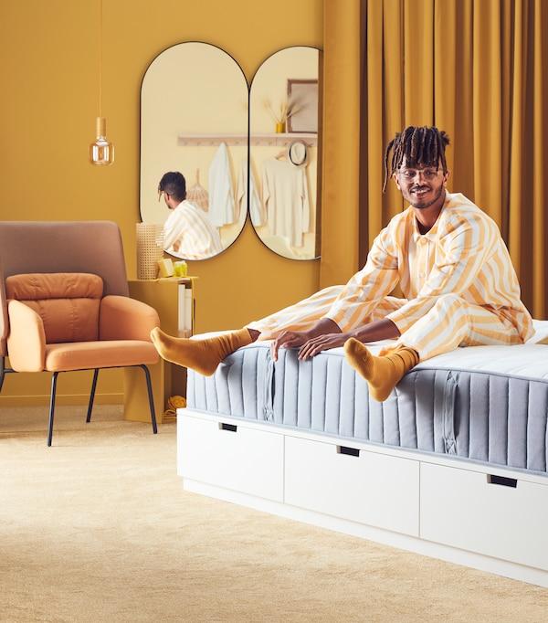 Uśmiechnięty mężczyzna siedzi na materacu VÅGSTRANDA w urządzonej na żółto sypialni
