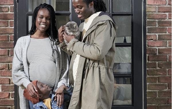 Usmievajúci sa muž s mačkou na rukách a tehotná žena pred tehlovou stenou s malým chlapcom uprostred.