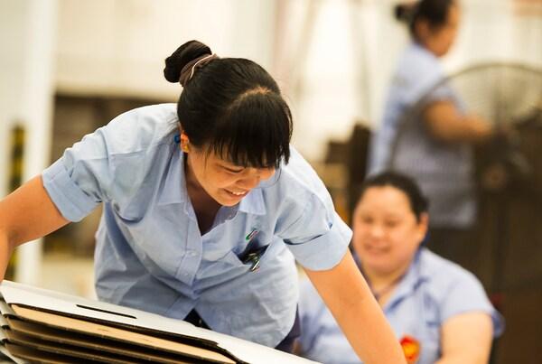 Усміхнена жінка, яка працює на підприємстві одного з постачальників ІКЕА, піднімає стос пласких білих картонних коробок.