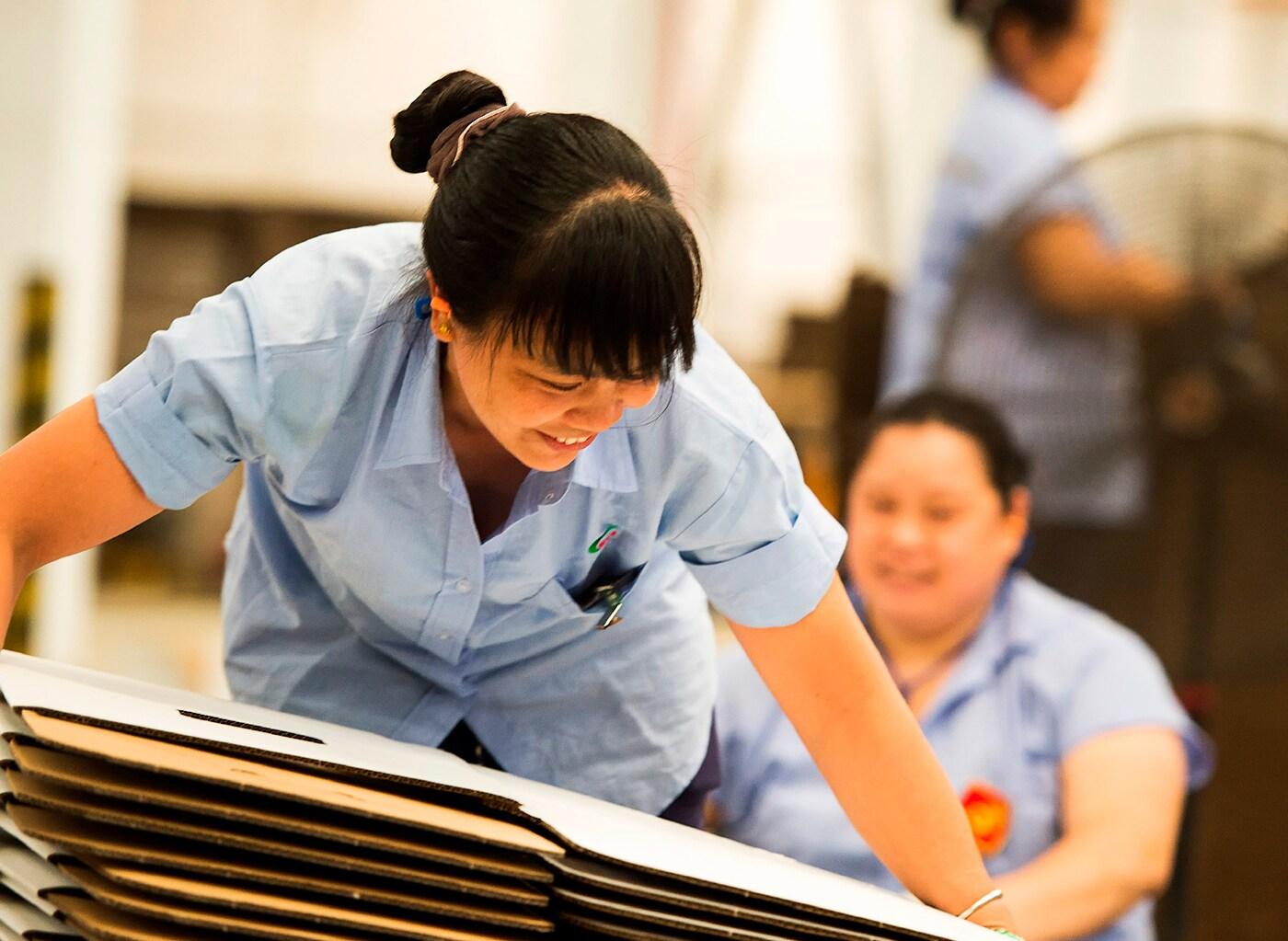Usmívající se žena pracující u dodavatele IKEA zvedá hromadu placatých kartonových obalů.