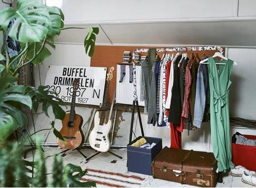 Usporiadajte otvorený šatník tak, aby pôsobil príjemne. Vešiak s oblečením, dve gitary na stojane, kufor a úložné škatule.