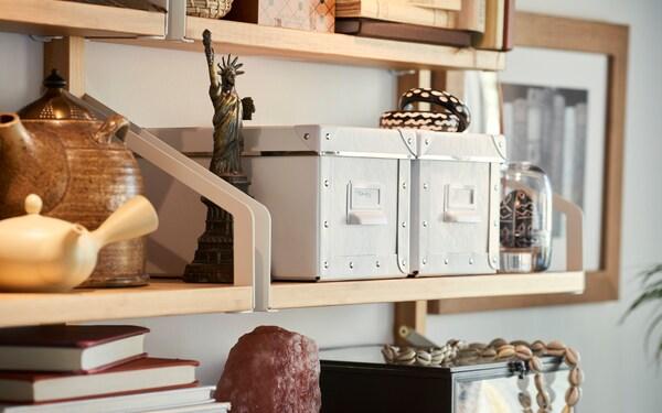 Ustaw na półkach kilka pudełek IKEA FJÄLLA, aby uporządkować i ochronić przed kurzem wszystkie drobiazgi i papiery.