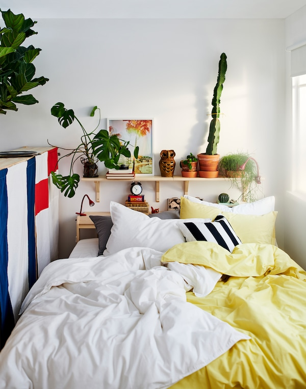 Ustawione między oknem i odwróconą tyłem szafką łóżko z mnóstwem poduszek oraz pościelą w kolorze żółtym, białym, czarnym i szarym.