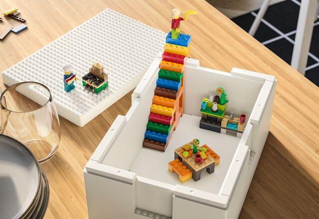 Ustawione na stole białe pudełko BYGGLEK z umieszczonymi w środku kolorowymi budowlami z klocków LEGO, między innymi schodami.