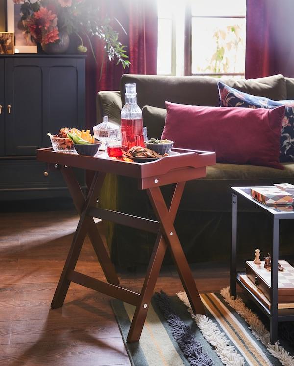 Ustawiony na pasiastym dywanie, obok oliwkowozielonej sofy, ciemnoczerwony stolik z tacą, na której znajdują się miski z przekąskami i karafka z sokiem.