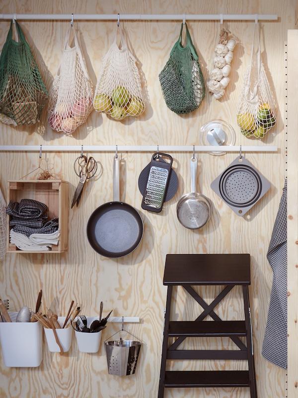 Ustensilele de bucătărie și sacoșele cu alimente atârnă de șine albe SUNNERSTA fixate pe un perete de placaj lângă un taburet negru, BECKVÄM.