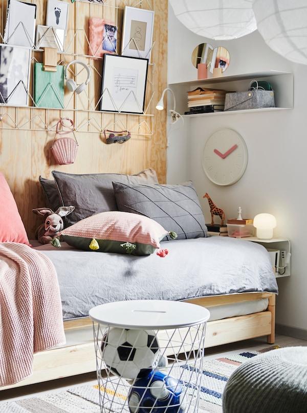 UTÅKER seng, der kan stables, med masser af puder, papirkunst på væggen over den, en BOTKYRKA væghylde brugt som sengebord, opbevaring og pynteting.