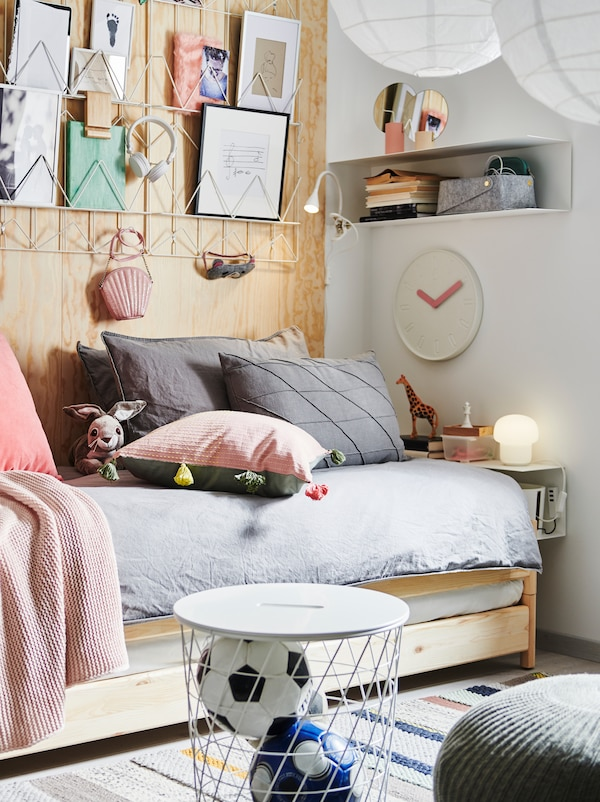 UTÅKER složivi krevet s puno ukrasnih jastuka, papirnim ukrasima iznad njega, BOTKYRKA policom pokraj kreveta, rješenjima za odlaganje i ukrasima.