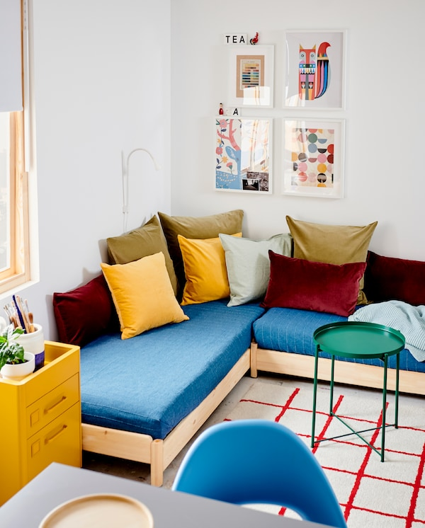 UTÅKER stackable bed is used as a corner sofa and has blue bedspreads and many cushions. A green tray table stands beside.