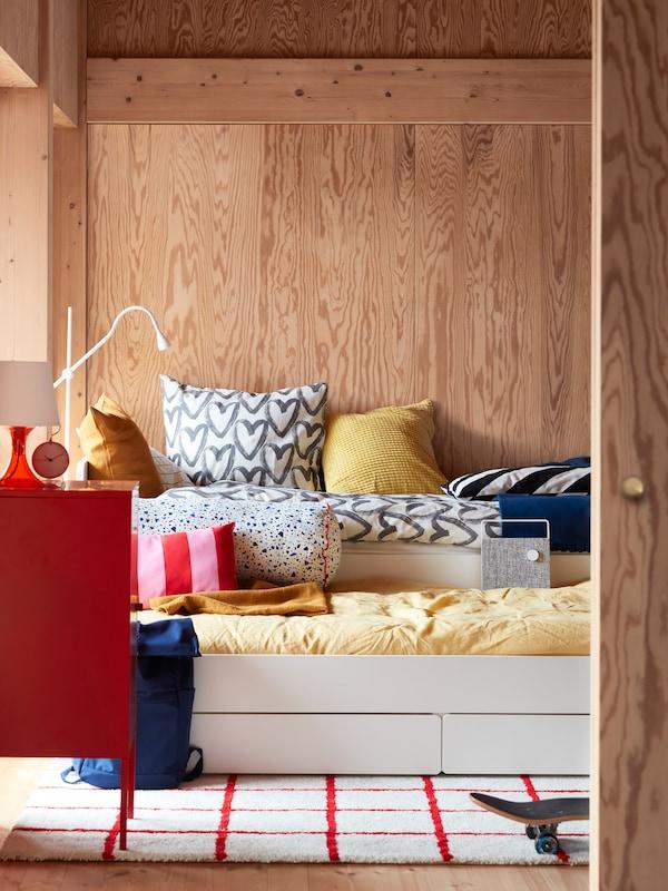 Utdragbar SLÄKT säng i ett sovrum med träpanel, bäddad med ett gult påslakanset och ett vitt med grå hjärtan.