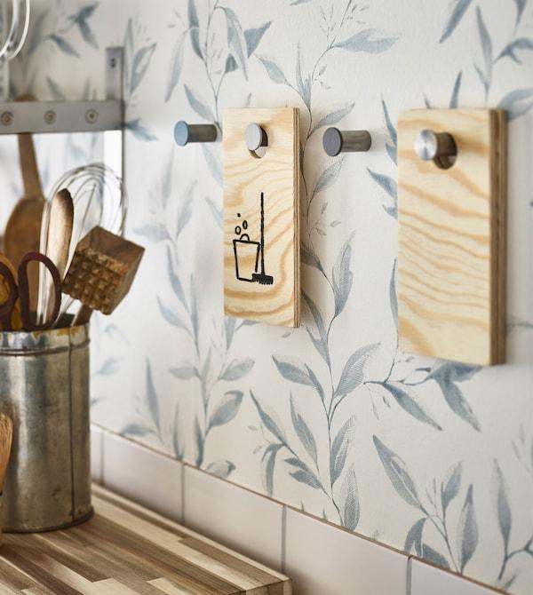 Utensilios de cocina en un contenedor metálico y ganchos en la pared sujetando etiquetas de tareas de madera caseras.
