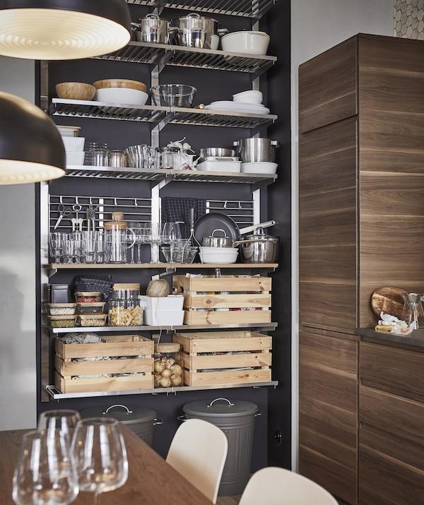 Utensilios de cocina, vajilla y cajas de madera almacenadas en un módulo de almacenaje abierto metalizado frente a una pared oscura.