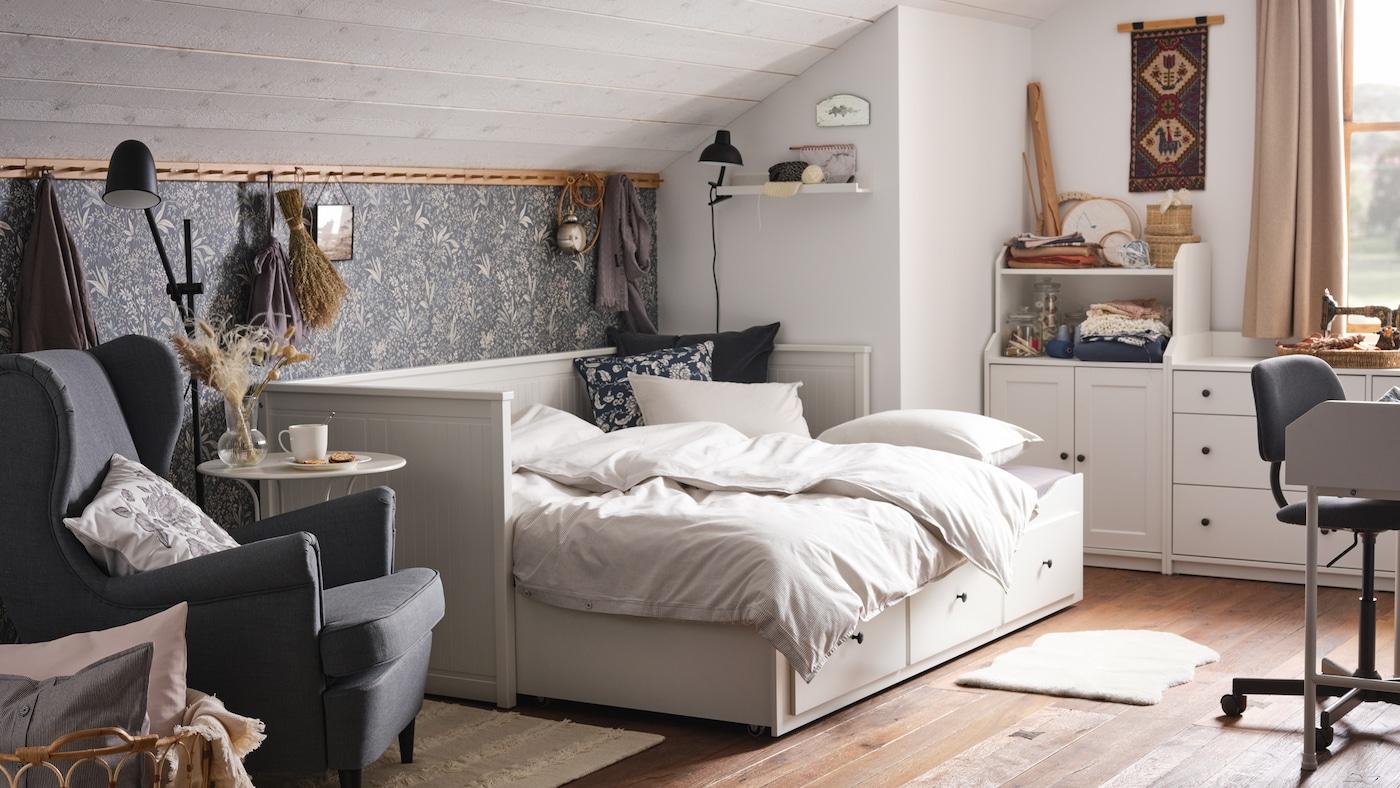 Útulná ložnice se zkoseným stropem, bílá pohovka se třemi zásuvkami a bílá úložná sestava.