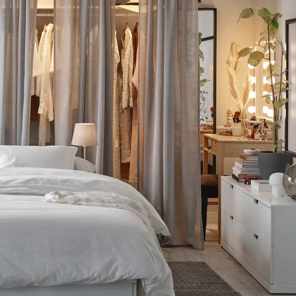 Útulná spálňa so závesmi a manželskou posteľou.