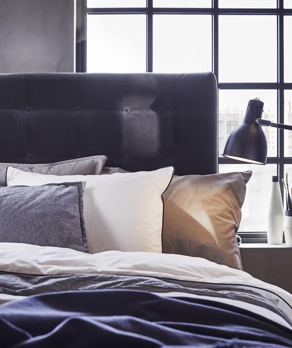 Uvećani prikaz kreveta sa slojevima jastuka i posteljine bijele i sive boje, tamnog uzglavlja i crne lampe na noćnom ormariću.