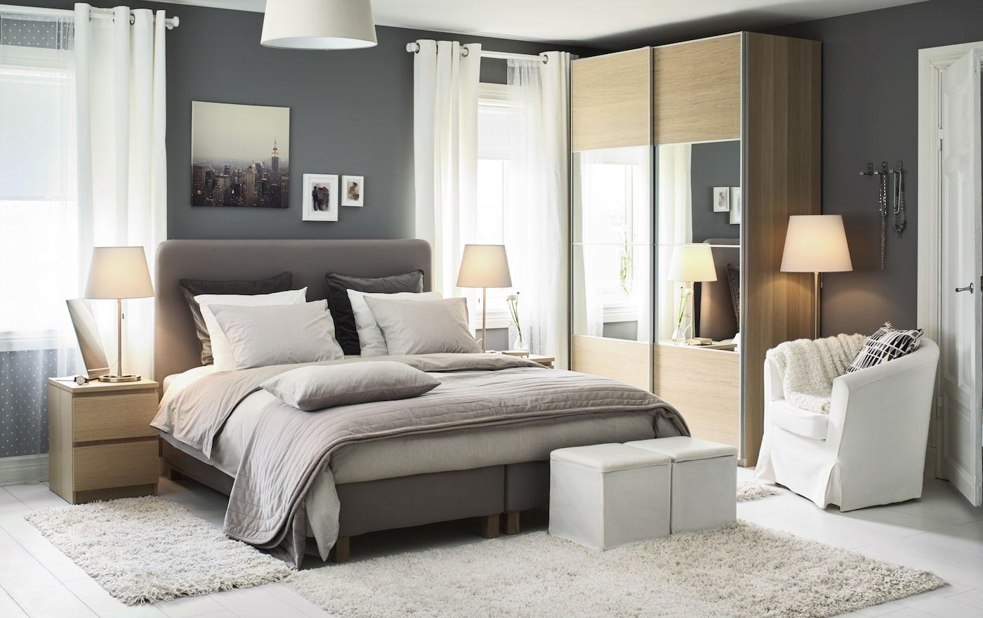 Уютная спальня: двуспальная кровать, тумбочки по обе стороны, с ночниками на них, в углу комнаты - шкаф с зеркалами. Над изголовьем висят несколько картин: на самой большой - урбанистический пейзаж, на той, что меньше - мужской силуэт в строгом костюме рядом с креслом, а на самой маленькой - человек.