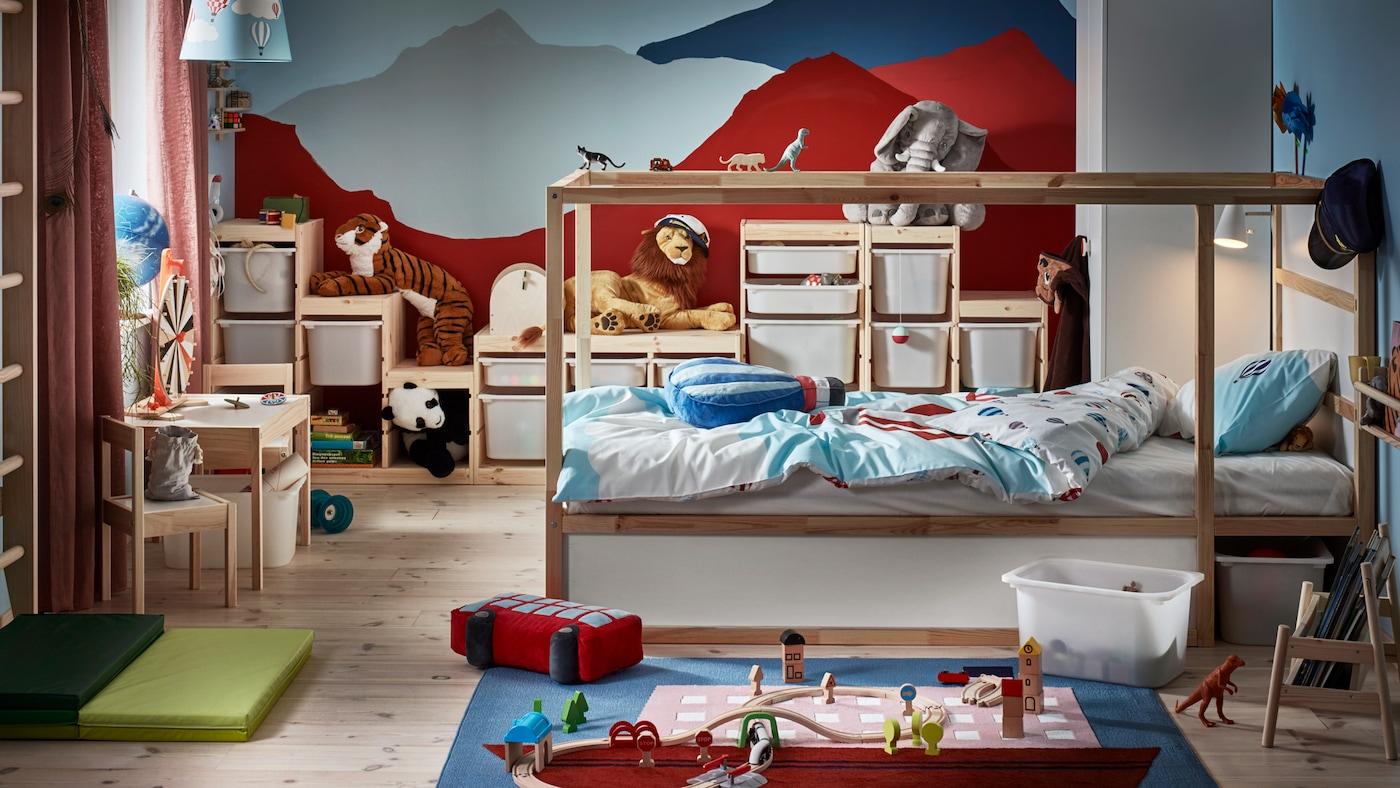 В детской стоит двусторонняя кровать КЮРА, на стене нарисован горный пейзаж, вокруг множество игрушек.