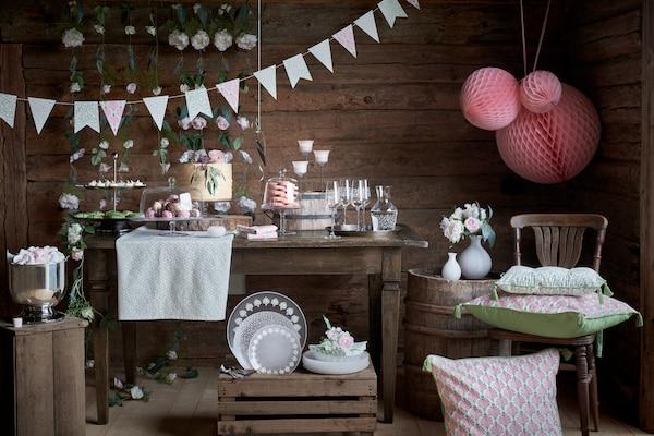 V kmečkem poslopju stojijo miza, steklene in namizne posode ter dekoracije iz INBJUDEN kolekcije.