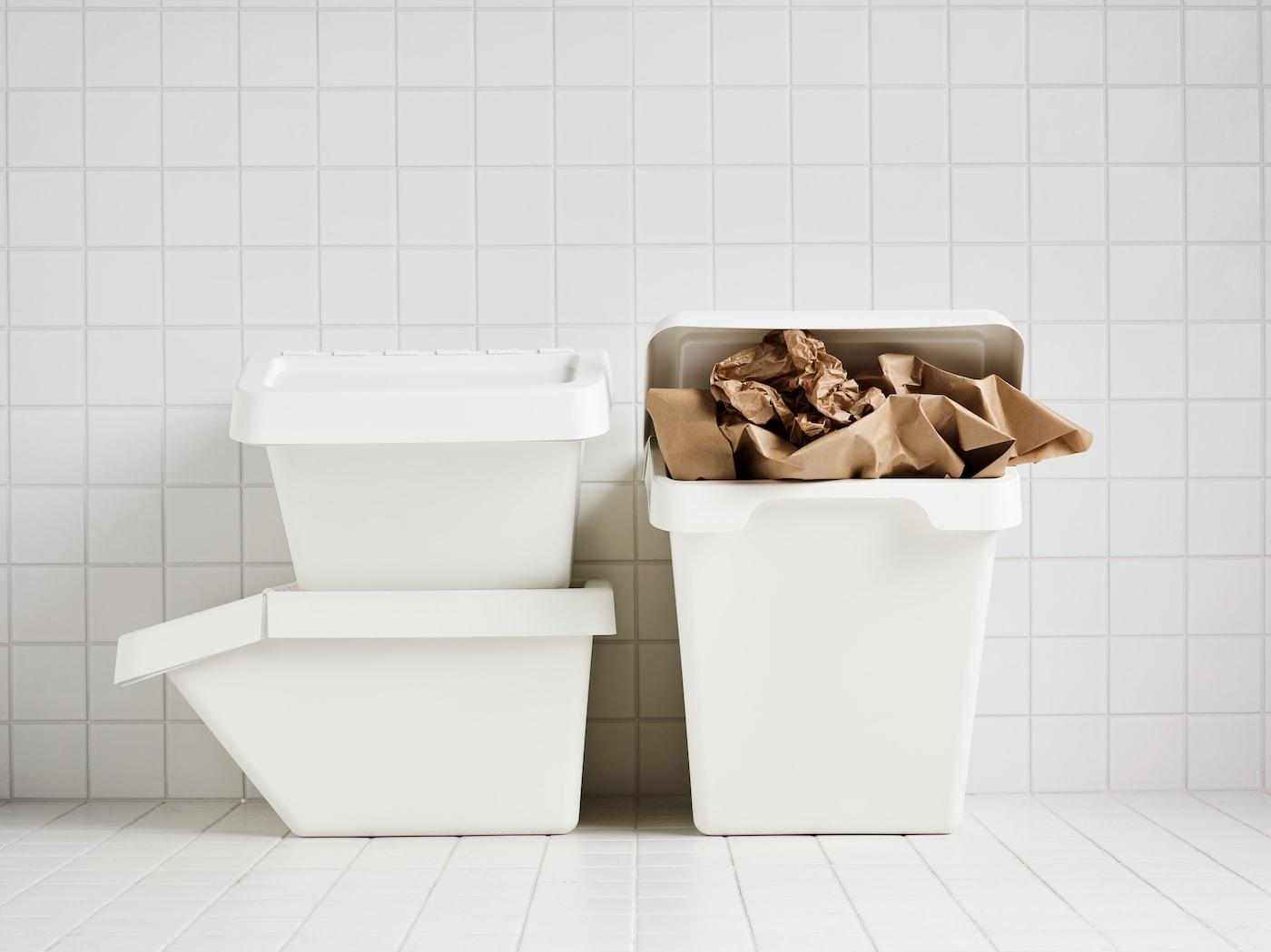 В комнате, облицованной белой плиткой, стоят три белых мусорных бака СОРТЕРА, один из них наполнен коричневой оберточной бумагой.