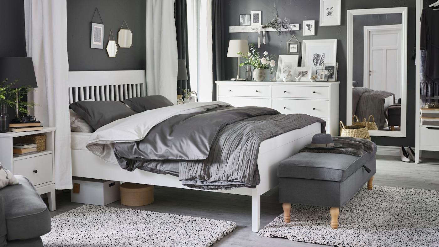 V ložnici stojí bílá postel IDANÄS, noční stolek a komoda, na posteli je ložní prádlo LUKTJASMIN.