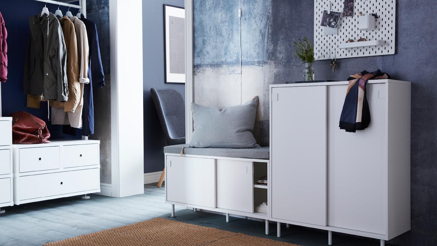 В прихожей скамья МАККАПЭР с отделением для хранения и серой подушкой сверху, рядом шкаф МАККАПЭР с вазой и шарфом.
