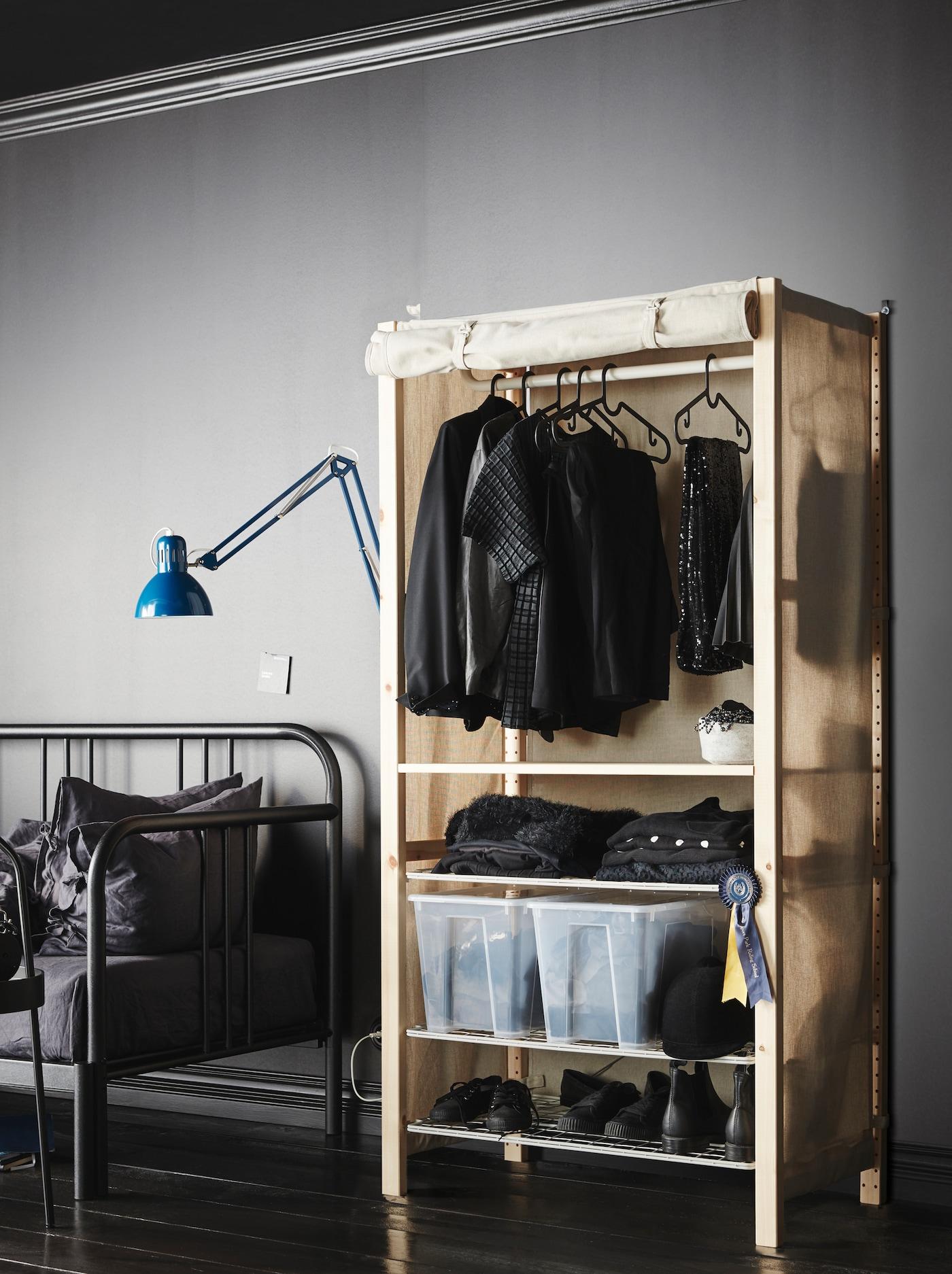 В серой комнате с минималистичным интерьером стоит стеллаж ИВАР с текстильным чехлом. Он играет роль гардероба с одеждой.