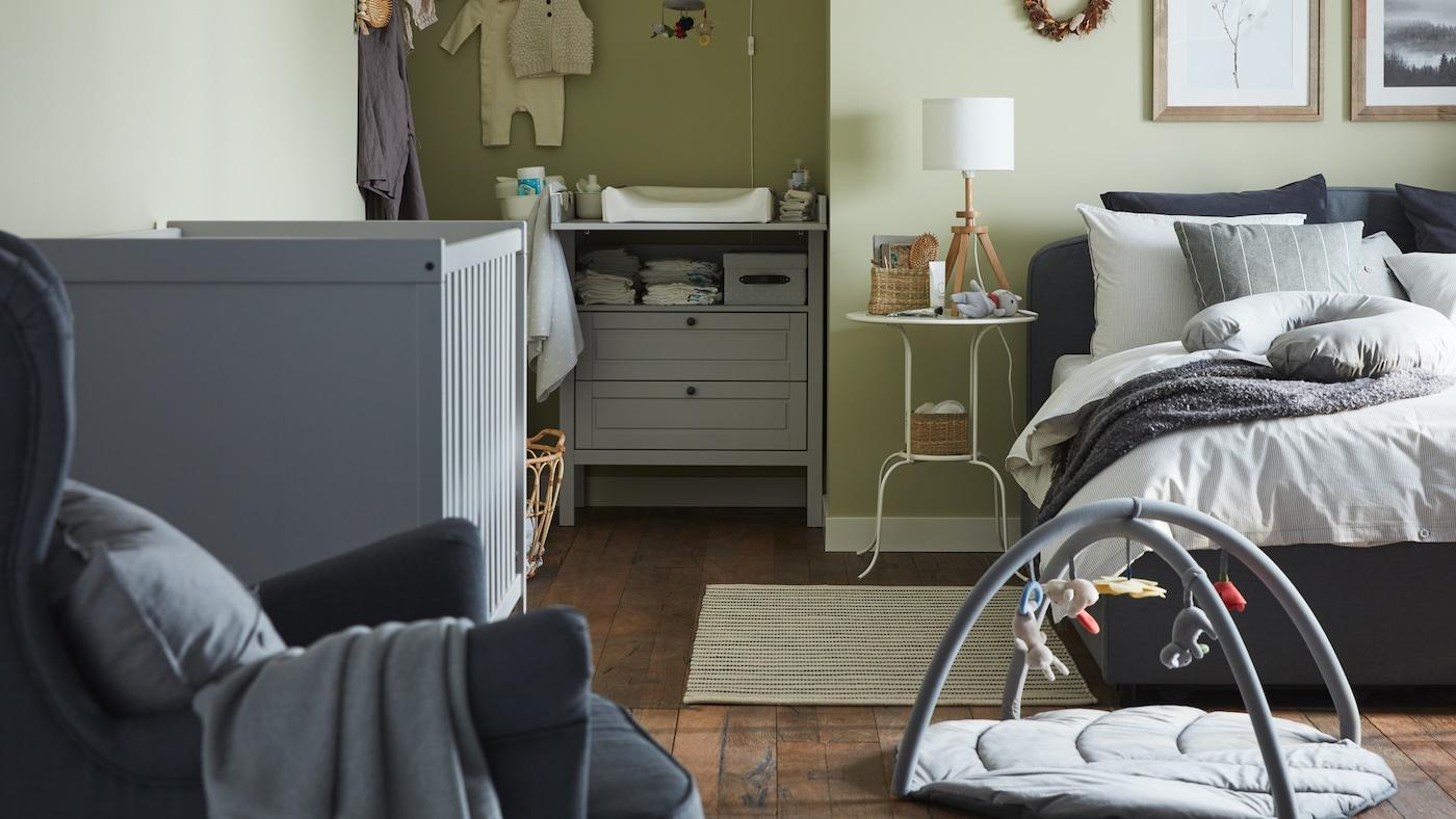 В спальне и детской комнате с зелеными стенами стоят кровать с серой обивкой, серая детская кроватка, серый пеленальный стол/комод.