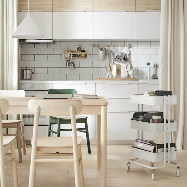 Vaalea keittiö, jossa on koivuinen jatkettava RÖNNINGE-ruokapöytä jonka vieressä on valkoinen RÅSKOG-tarjoiluvaunu. Tarjoiluvaunussa on etätyöskentely tarvikkeita.