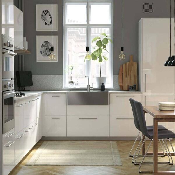 Vaalea keittiö jossa on valkoiset kaapin ovet ja laatikot.