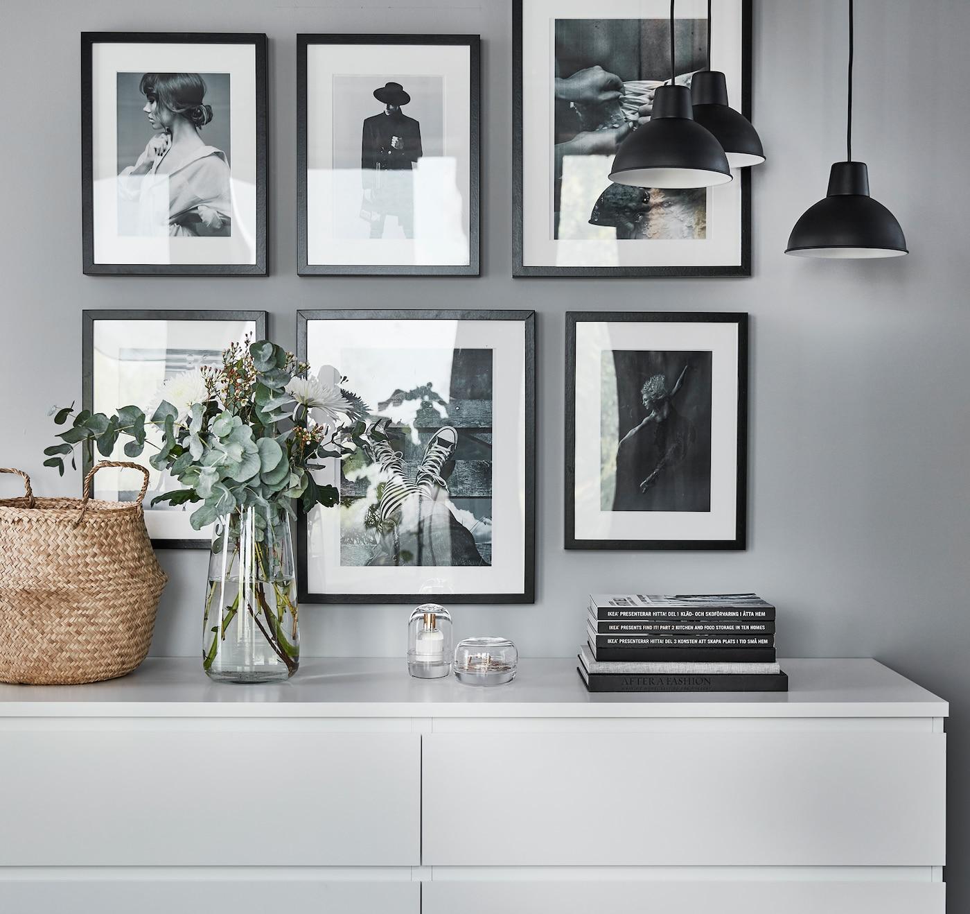 Vaalea lipasto, kukkakimppu ja seinä jossa useita kauniita mustavalkoisia valokuvia mustissa kehyksissä.