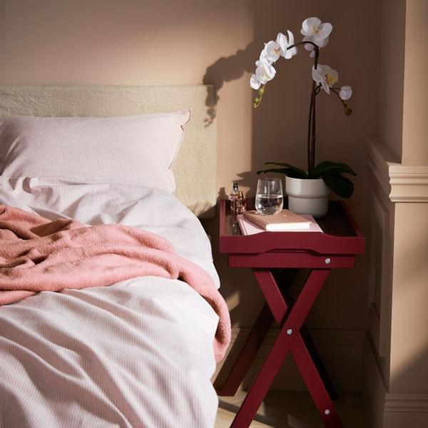 Vaalea makuuhuone, jossa vaaleanpunaiset tyynyt ja peitot, beiget verhot ikkunan edessä.