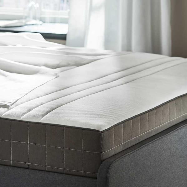 Vaalea patja tummanharmaassa sängynrungossa.