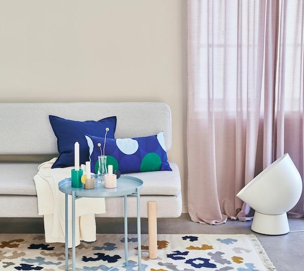 Vaalea sohva, sininen sohvapöytä ja valkoinen valaisin beigessä olohuoneessa