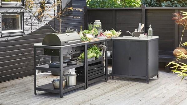 Vaalealla puuterassilla on harmaa, grillillä varusteltu GRILLSKÄR-minikeittiö harmaan puuseinän vieressä.