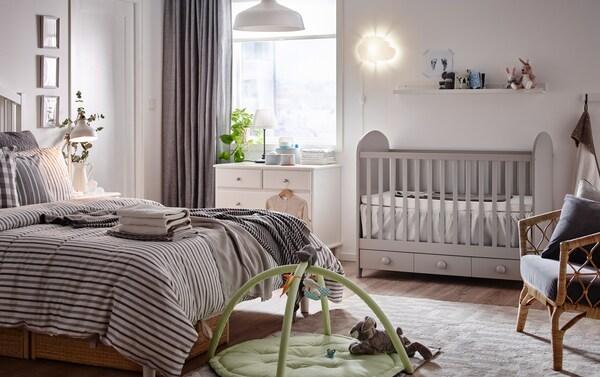 Vaaleanharmaa pinnasänky vaaleasävyisessä vanhempien makuuhuoneessa.