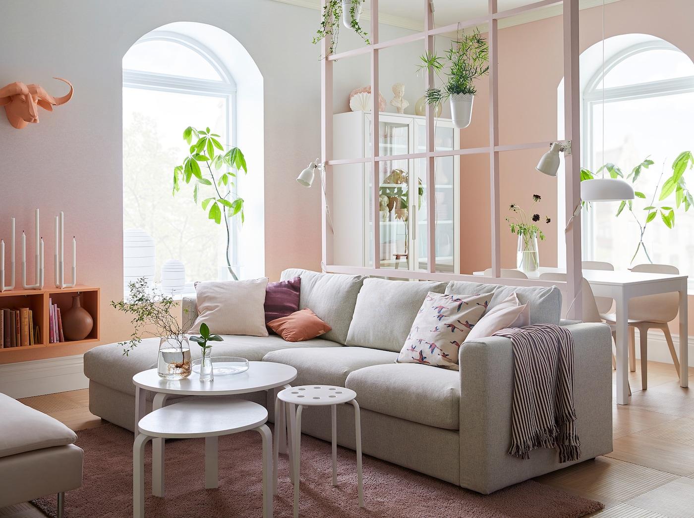 Vaaleanpunainen ja valkoinen olohuone, jossa on liukuvärjätyt seinät, beige sohva divaanilla. Ruokailutila näkyy taustalla.