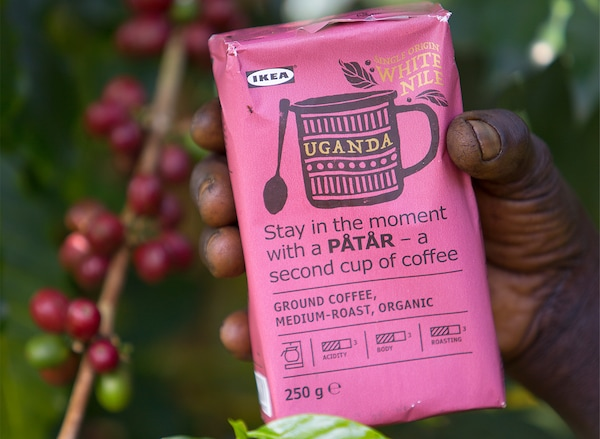 Vaaleanpunainen kahvipaketti, PÅTÅR special edition 100 % Arabica-kahvia, kahvinviljelijän kädessä.