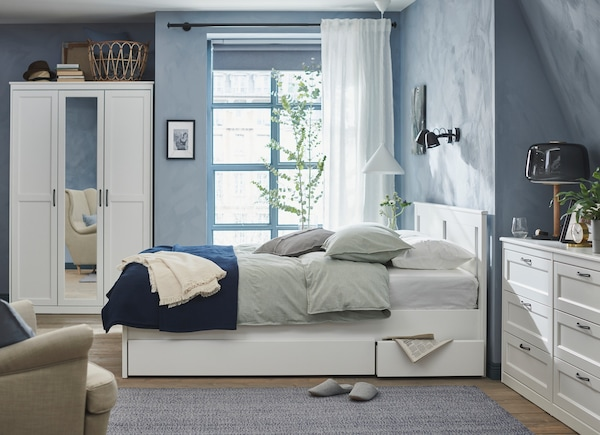 Vaaleansininen makuuhuone, jossa valkoinen sänky, vaatekaappi ja lipasto