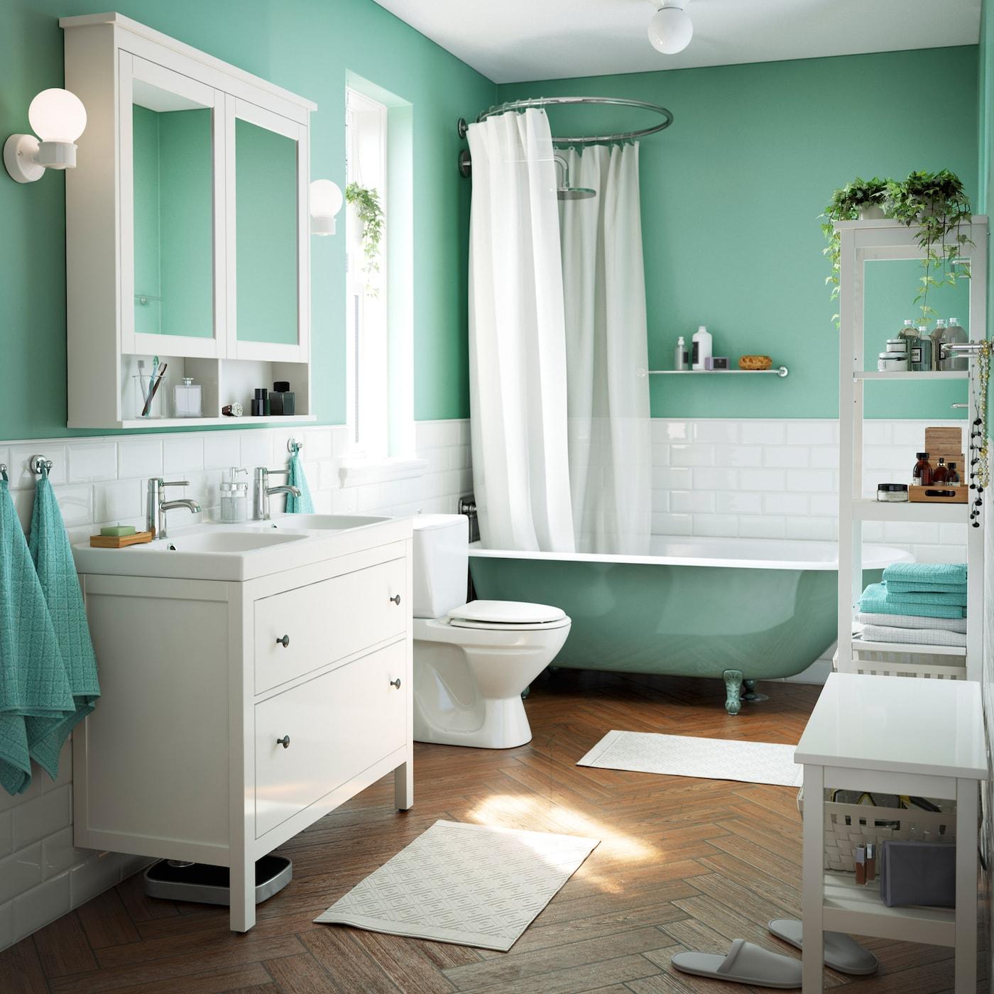 Vaaleanvihreä, mintunvihreä ja valkoinen kylpyhuone, jossa perinteinen kylpyamme ja kaksi pesuallasta. Tassukylpyamme on viehättävän vanhanaikainen.