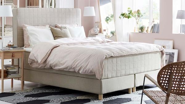 Vaaleasävyinen makuuhuone, vaalea sänky, peitto, tyynyjä. Etualalla tuoli. Sängyn vieressä sivupöytä.