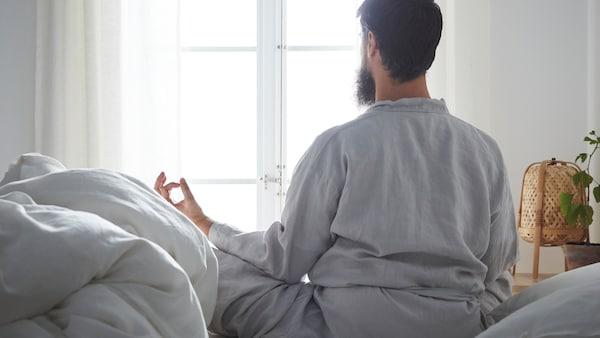 Vaalein sävyin sisustetussa makuuhuoneessa mies istuu sängyllä ja meditoi katsoen ikkunan suuntaan.