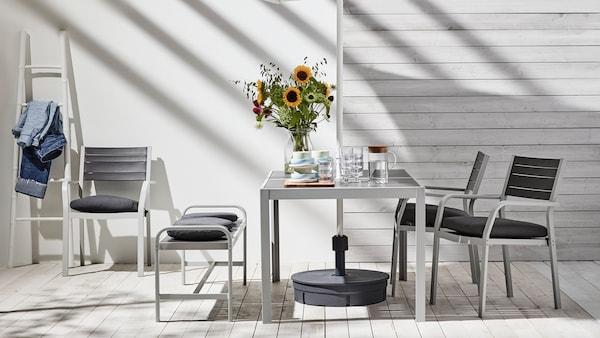 Vaalenaharmaa SJÄLLAND-pöytä tummanharmaalla pöytälevyllä ja SJÄLLAND-tuolit tummanharmailla istuinosilla.