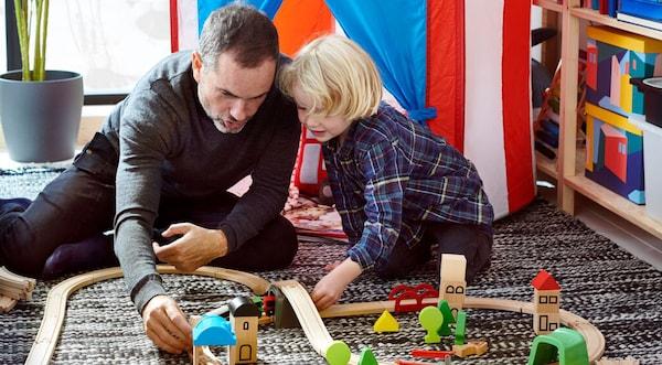Vader speelt met kind onringd door speelgoed