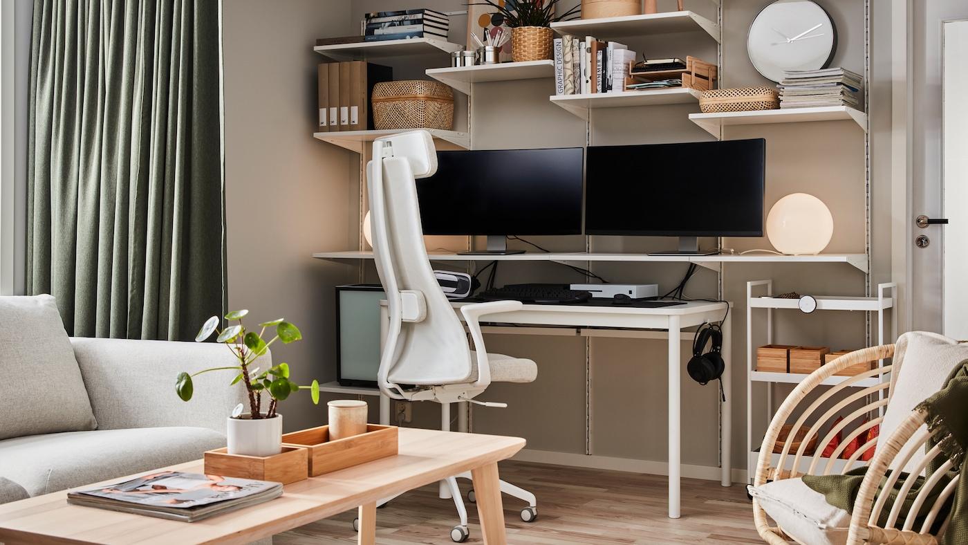 Väggmonterade hyllor med två datorskärmar och böcker, soffbord i askfaner och beige/vit kontorsstol.