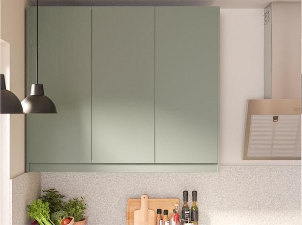 Vægmonterede køkkenskabe med grågrønne fronter, der har glatte og praktiske overflader, som er modstandsdygtige over for fugt og pletter.