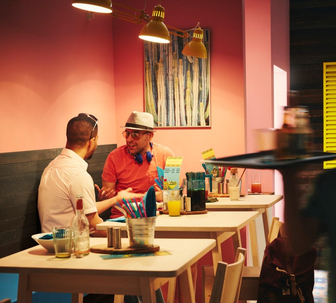 Värikkäät seinät sopivat etnisen ravintolan tyyliin. Koivunväriset IKEA NORRÅKER tuolit ja pöydät täydentävät yhteensopivan kokonaisuuden.