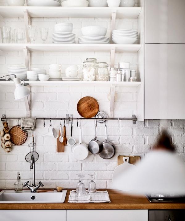 Vajilla blanca colocada en estantes abiertos por encima de un fregadero y encimera de madera.